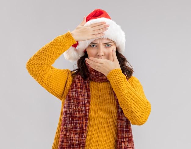 Ernstige jonge slavische meisje met kerstmuts en met sjaal om nek legt hand op voorhoofd en mond geïsoleerd op een witte muur met kopieerruimte