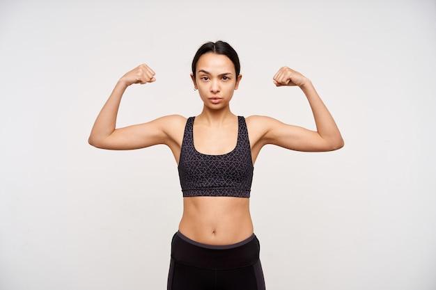 Ernstige jonge sportieve bruinharige vrouw die haar handen opheft terwijl ze sterke biceps demonstreert en serieus naar de voorkant kijkt, geïsoleerd over een witte muur