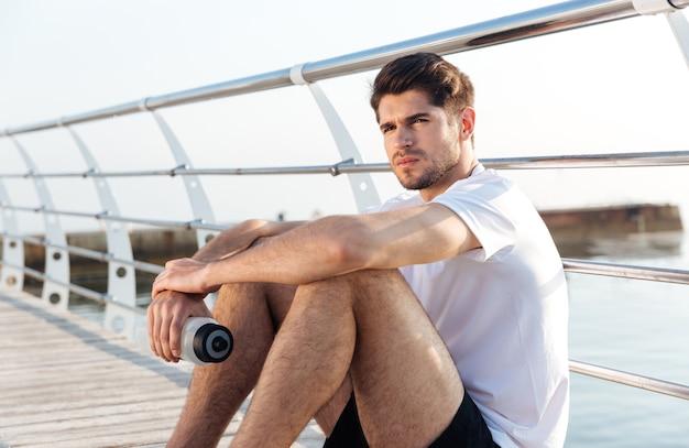 Ernstige jonge sportman met fles water zittend op de pier