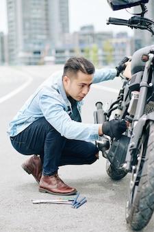 Ernstige jonge vietnamese man die problemen heeft met de motorfiets, hij repareert hem onderweg