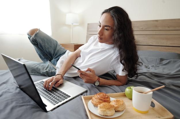 Ernstige jonge vietnamese man met golvend haar liggend op bed met dienblad met broodjes, koffie en appel en met behulp van moderne apparaten in de slaapkamer