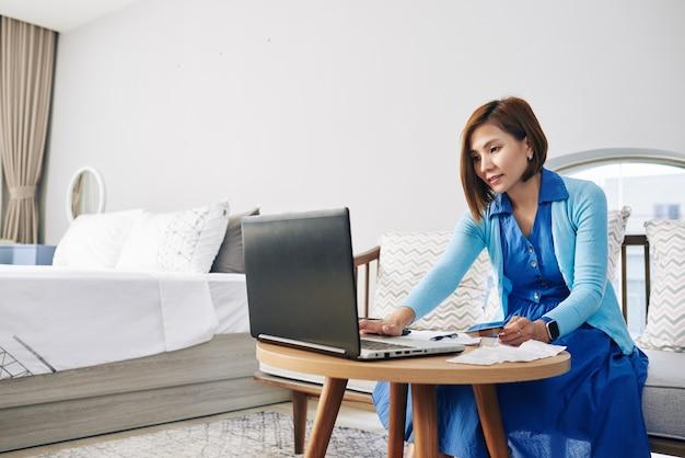 Ernstige jonge vietnamese vrouw die rekeningen controleert en factuurdocument online invult