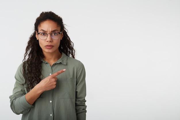 Ernstige jonge, vrij donkere vrouw met bruin krullend haar, fronsende wenkbrauwen terwijl ze serieus opzij wijst met wijsvinger, staande op een witte achtergrond