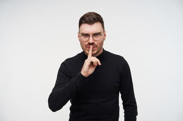 Ernstige jonge vrij kortharige bebaarde brunette man fronst zijn wenkbrauwen terwijl hij serieus kijkt en de wijsvinger op zijn lippen houdt, geïsoleerd op wit