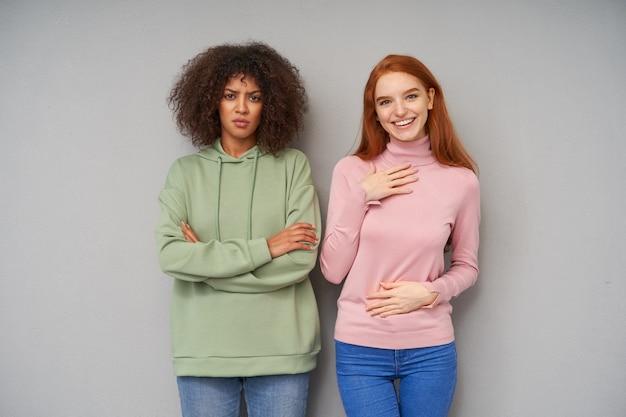 Ernstige jonge vrij krullende donkere huid brunette vrouw in groene hoodie en spijkerbroek handen op haar borst kruisen en wenkbrauwen fronsen terwijl ze met haar vriendin over de grijze muur staat
