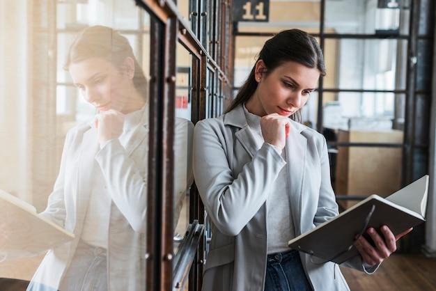 Ernstige jonge vrouw die agenda op kantoor bekijkt