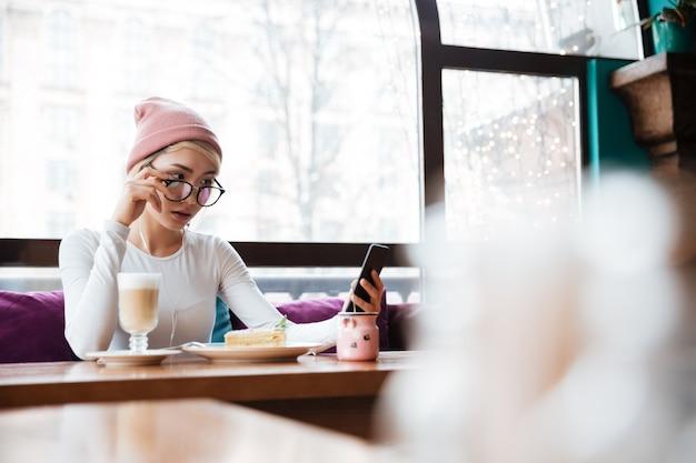 Ernstige jonge vrouw die en celtelefoon in koffie eet met behulp van
