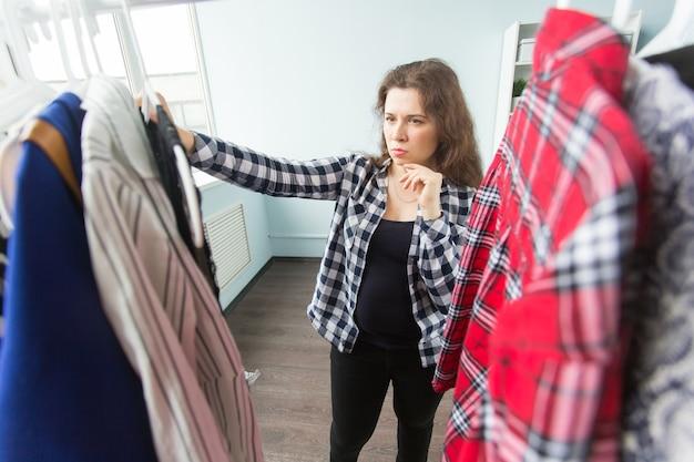 Ernstige jonge vrouw die kleren in haar garderobe kiest.