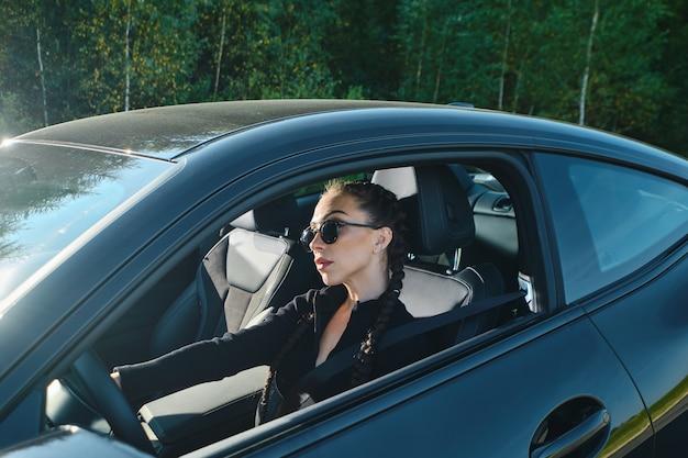 Ernstige jonge vrouw die krachtige auto drijft op een landweg
