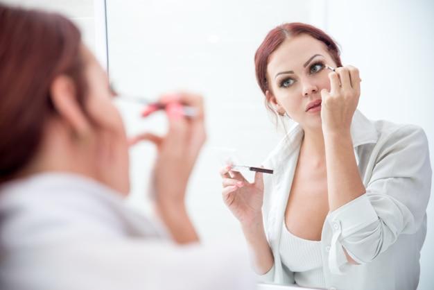Ernstige jonge vrouw die oogschaduw toepast bij spiegel