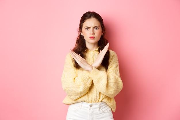 Ernstige jonge vrouw fronst, kijkt vastberaden, maakt een kruisblokgebaar, verbiedt iets slechts, zegt nee, staat over roze muur