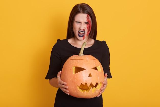 Ernstige jonge vrouw, gekleed in zwarte jurk, op zoek schreeuwend, dame spreekt woede, meisje in halloween kostuum geïsoleerd op geel met pompoen in handen.