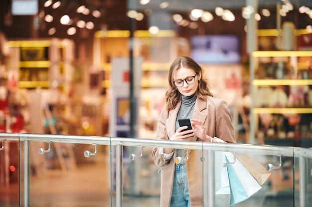 Ernstige jonge vrouw in brillen die zich bij traliewerk bevinden en smartphone in wandelgalerij controleren