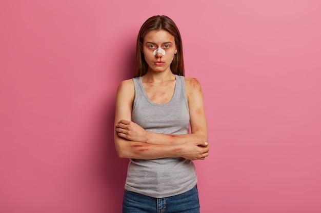 Ernstige jonge vrouw kreeg bloedneus na een ongeval, houdt armen over de borst gevouwen, slachtoffer van huiselijk geweld, geslagen door iemand, poseert tegen roze muur, heeft gekneusde huid. wreed sadisme