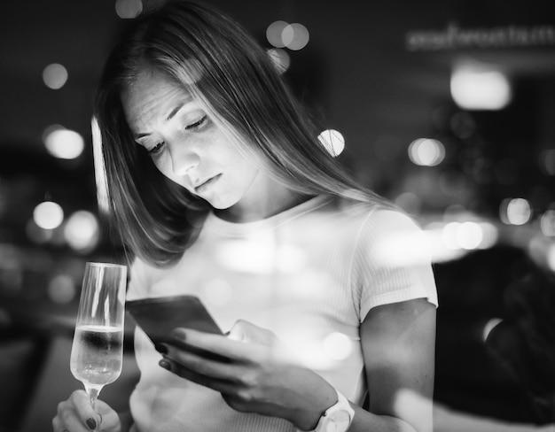 Ernstige jonge vrouw met behulp van een smartphone bij een bar op het dak in de e