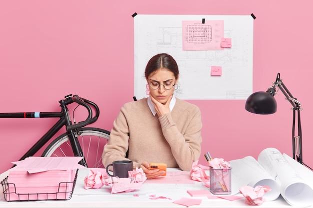 Ernstige jonge vrouw met bril maakt schetsen en blauwdrukken in kantoor met smartphone, poseert op desktop tegen roze muur. professionele grafisch ontwerper ontwikkelt nieuwe strategie