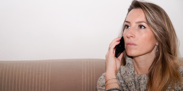 Ernstige jonge vrouw praten op mobiele telefoon thuis sofa op websjabloon voor spandoek koptekst
