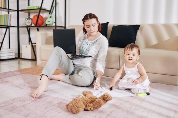 Ernstige jonge vrouw zittend op de vloer thuis, e-mails en financiële documenten controleren wanneer haar dochtertje dichtbij speelt