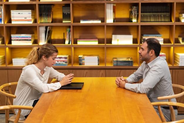 Ernstige jonge vrouw zittend op een interview en het gebruik van de mobiele telefoon