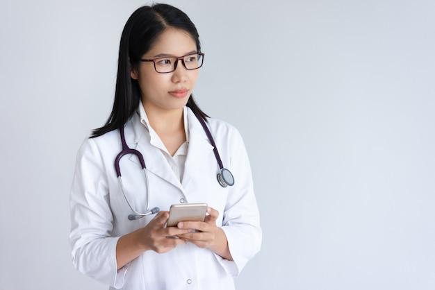 Ernstige jonge vrouwelijke arts met behulp van smartphone