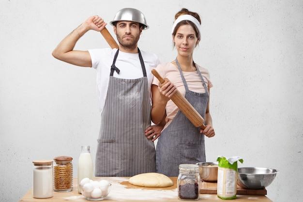 Ernstige jonge vrouwelijke en mannelijke stand op kirchen in de buurt van tafel met producten