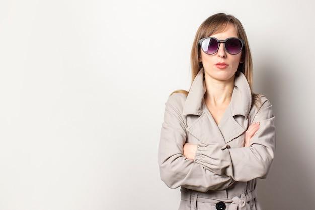Ernstige jonge vrouwen in zwarte zonnebril en gekleed in een beige mantel, armen over haar borst. het model is koppig en zelfverzekerd en poseert op een lichte muur. lege ruimte voor tekst