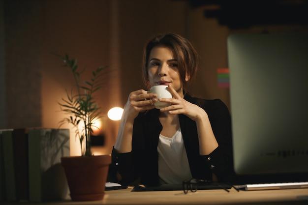 Ernstige jonge vrouwenontwerper bij nacht die computer met behulp van