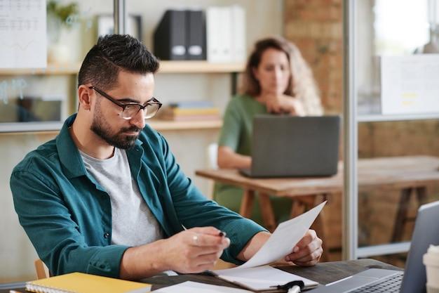 Ernstige jonge zakenman in brillen zittend op zijn werkplek voor laptop en het lezen van een contract op kantoor