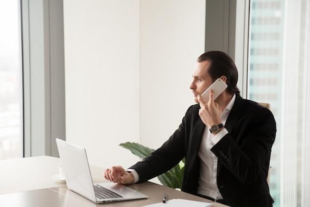 Ernstige jonge zakenman in bureau die telefoongesprek maken.