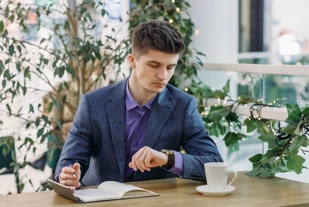 Ernstige jonge zakenman in een pak rust in een straatcafé, schrijft in een notitieblok en kijkt naar zijn horloge terwijl hij de tijd controleert