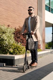 Ernstige jonge zakenman in elegante vrijetijdskleding en zonnebril die zich op elektrische autoped langs muur van eigentijds zakencentrum bewegen