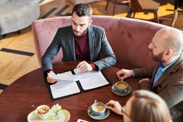 Ernstige jonge zakenman in jasje aan tafel zitten en contract met nieuw financieel bedrijf in restaurant lezen
