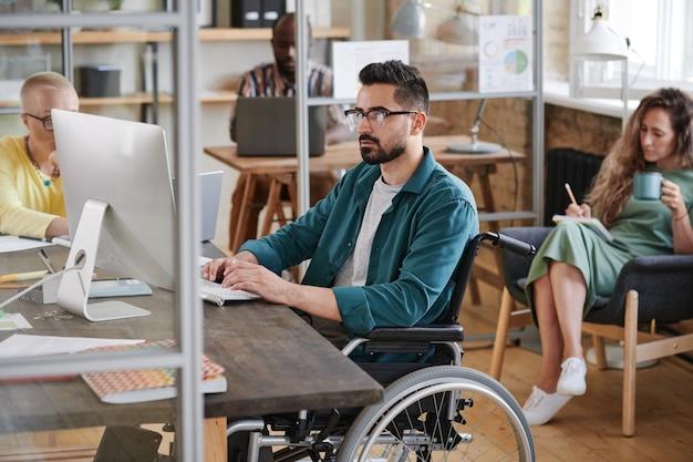 Ernstige jonge zakenman in rolstoel zittend aan tafel en typend op de computer die hij op kantoor werkt met zijn collega's