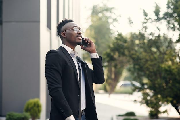 Ernstige jonge zakenman in zwart pak