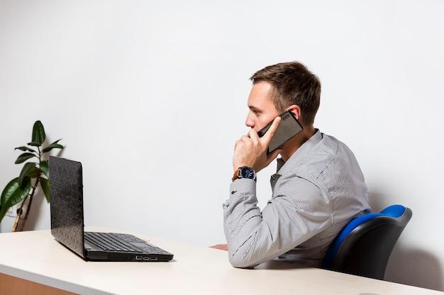 Ernstige jonge zakenman zit aan de tafel op kantoor met een laptop en praat op zijn mobiele telefoon