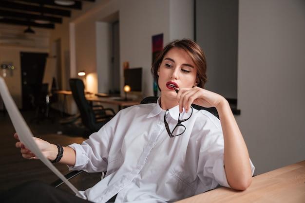 Ernstige jonge zakenvrouw die een zonnebril vasthoudt en naar een blauwdruk op kantoor kijkt