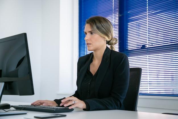 Ernstige jonge zakenvrouw jas dragen, computer gebruiken op de werkplek op kantoor, typen en kijken naar display. gemiddeld schot. digitaal communicatieconcept