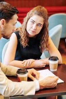 Ernstige jonge zakenvrouw luisteren naar ideeën van haar collega of zakenpartner tijdens bijeenkomst in café