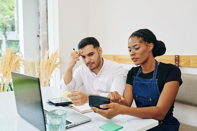 Ernstige jonge zwarte serveerster die calculator met som van uitgaven toont aan haar fronsende collega