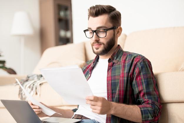 Ernstige jongeman en bril kijken door financiële documenten terwijl u thuis kantoor werkt