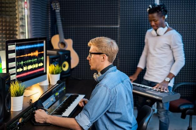Ernstige jongeman in denim overhemd zit achter computerscherm en werkt met geluidsgolfvormen terwijl een andere man pianobord speelt