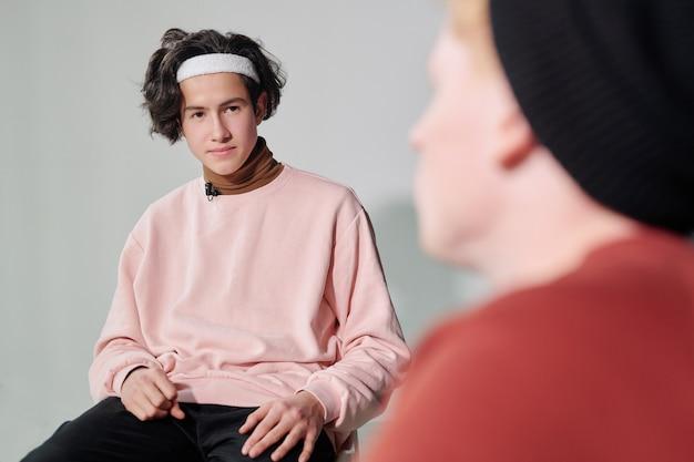 Ernstige jongeman in poederachtige roze trui en witte hoofdband interactie met vlogger zit voor hem
