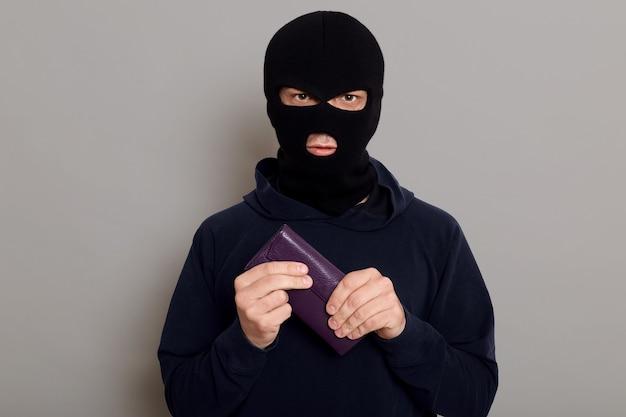 Ernstige jongeman inbreker in overvalmasker en zwarte trui houdt de portemonnee stevig vast die hij net heeft gestolen