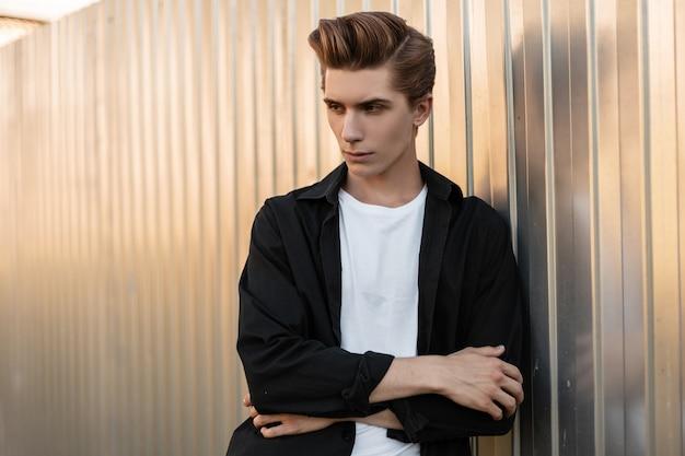 Ernstige jongeman met een modieus kapsel in een stijlvol t-shirt in een vintage zwart shirt i