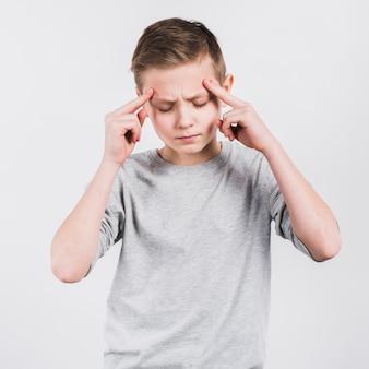 Ernstige jongen die hoofdpijn hebben die zich tegen witte achtergrond bevinden