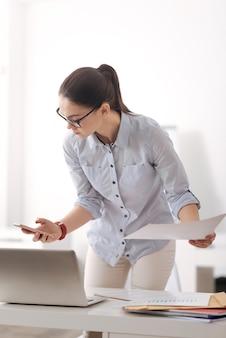 Ernstige kantoormedewerker die de telefoon in de rechterhand houdt en het document in de linker houdt terwijl ze naar haar apparaat kijkt