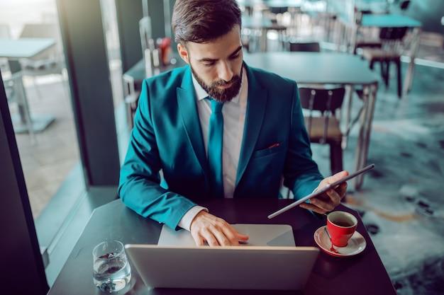 Ernstige kaukasische bebaarde zakenman in pak met behulp van tablet en laptop tegelijkertijd zittend in café. op bureau koffie. het kost tijd voor succes, wees geduldig en kijk er naar uit.