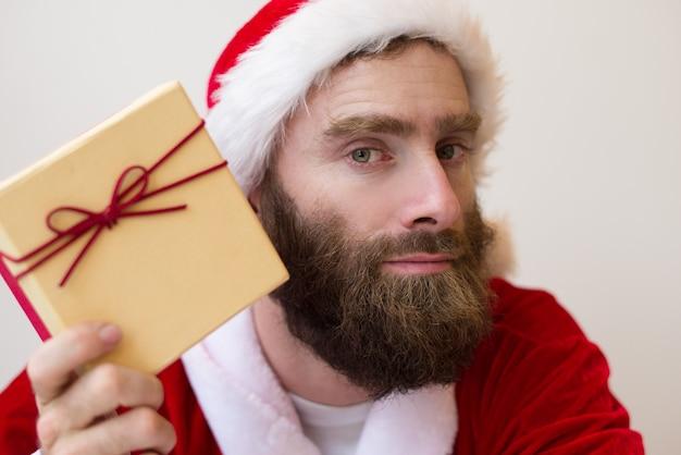 Ernstige kerel die het kostuum van de kerstman draagt en de doos van de gift houdt