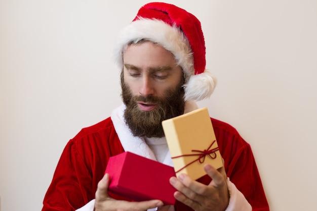 Ernstige kerel die het kostuum van de kerstman draagt en de doos van de gift onderzoekt