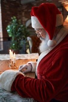 Ernstige kerstman in rode dop en bril zittend aan houten tafel met brandende kaarsen en lezen ...